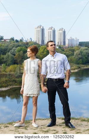 Beautiful young couple looking to future near the river