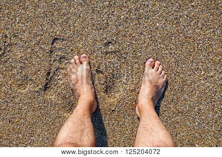 Male bare feet standing on the wet sandy beach