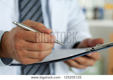 Male medicine doctor hand holding silver pen writing something on clipboard closeup. Ward round patient visit check medical calculation and statistics concept. Physician ready to examine patient