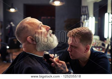 Barber making haircut to handsome attractive senior man with beard and working with electric razor in modern barber shop