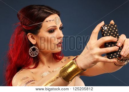Portrait of beautiful mysterious oriental woman with smartphone