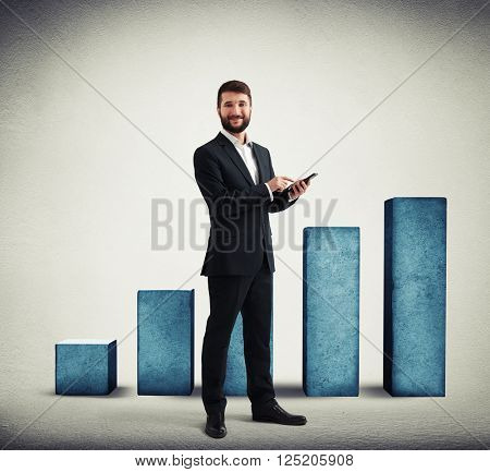 Young businessman in a formal wear with black phone in his hands on rising chart background