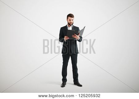 Man in a black formal wear and white shirt familiarize with the materials in the folder