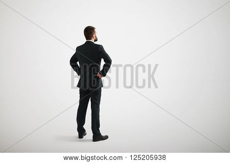 Man in a black business suit looks to the side with arms akimbo