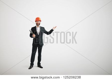 Smiling man in formal wear and a construction helmet points hand toward
