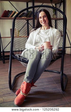 Laughing girl sitting in a chair with a cup, soft side light