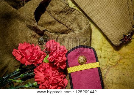 Carnations with forage-cap and ammunition belt on dark background