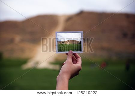 a young girl holding an instant photo like a polaroid in front of a landscape that is the same but a close up instead of a wide angle