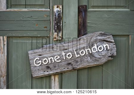 Gone to london sign on old green doors.