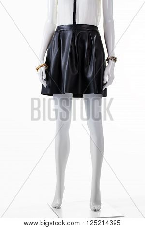 Short leather skirt on mannequin. Dark skirt and wrist accessories. Stylish skirt with small watch. Young lady's outfit for evening.