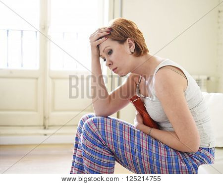 young beautiful red hair woman holding hot water bottle in a hurting belly suffering stomach cramp and period pain sitting on home couch in painful face expression female menstruation concept