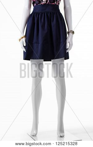 Short navy skirt on mannequin. Short skirt and wrist accessories. Young lady's dark casual clothes. New skirt at fashion house.