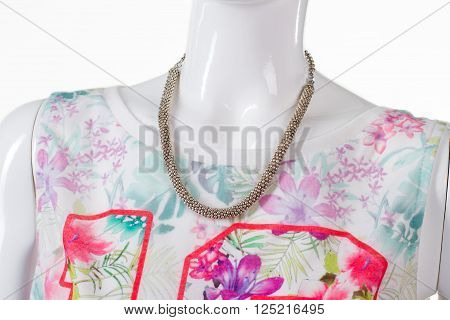 Colorful floral top with necklace. Simple metal necklace on mannequin. Girl's bright top and accessory. Bijouterie that matches summer clothing.