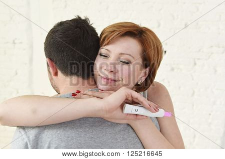 young happy woman hugging husband holding positive result pregnancy test expecting a baby in excited future parents love and happiness and family concept