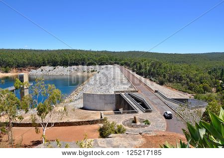 Views of Serpentine Dam with the Serpentine River basin, spillway and bridge bordered by a lush green forest under a clear blue sky in Serpentine, Western Australia.