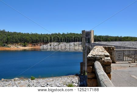Views of Serpentine Dam with the Serpentine River basin and bridge bordered by a lush green forest under a clear blue sky in Serpentine, Western Australia.