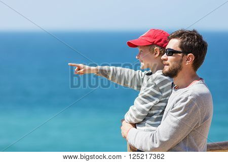 young father with a beard and his little son pointing at something with finger with beautiful blue ocean in the background enjoying time together