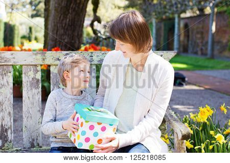 young beautiful mother and her adorable son sitting together in the park at spring time celebrating mother's day, boy giving her mother present and looking at each other