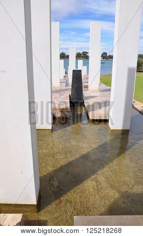 MANDURAH,WA,AUSTRALIA-MARCH 7,2014: Mandurah War Memorial with white pillars and fountain running into the Peel-Harvey Estuary in Mandurah, Western Australia.