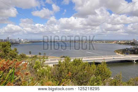 Elevated view of the Swan River and roadway with urban architecture from King's Park in Perth, Western Australia under a blue sky with clouds.