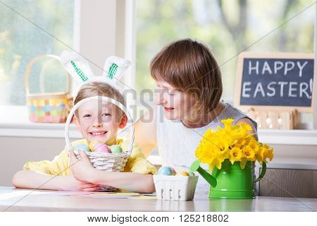 happy smiling family of two enjoying easter time at home, doing crafts, little boy with bunny ears holding basket with colorful easter eggs, easter themed decorations and blackboard sign