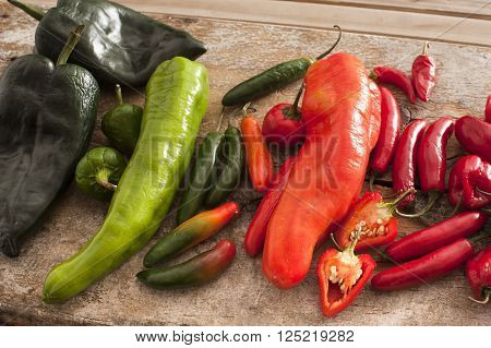 Large assortment of freshly picked green and red hot peppers displayed on a rustic table
