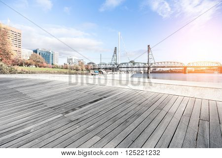 empty wood floor with luxury yacht and bridge at sunrise in portland
