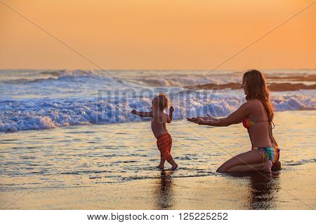 Family swimming fun in sea beach surf Happy mother baby son first step - toddler run to ocean wave on sunset sky background Child outdoor activity parent lifestyle summer holiday in tropical island
