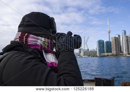Toronto Canada - January 27 2016: Person taking photos of Toronto skyline from a ship Ontario Canada.