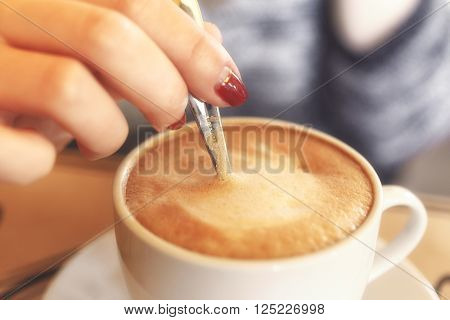 Closeup of a girl stirs the coffee with crema in a cafe. A mug of cappuccino with foam closeup