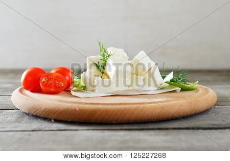 Slices feta cheese with dill, cherry tomatoes and spinach leaves on rustic wooden table on a wooden board