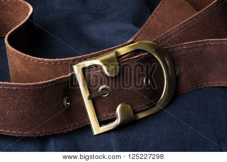 closeup of the brown suede strap with yellow metal buckle