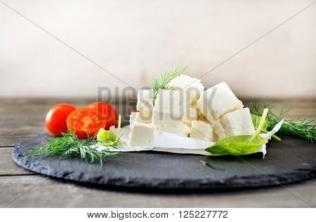 Sliced feta cheese with dill, cherry tomatoes and spinach leaves on wooden table on a black ceramic board, front view