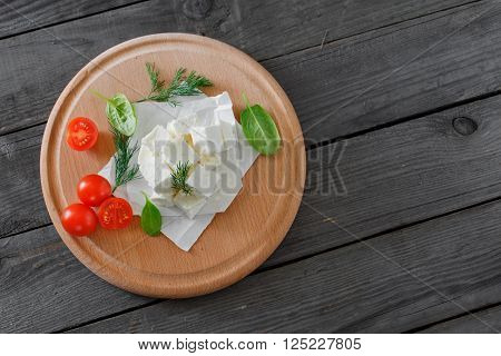 Sliced feta cheese with dill, cherry tomatoes and spinach leaves on wooden table on a wooden board, top view with copy space