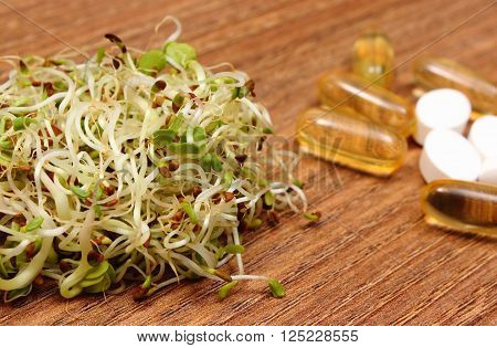 Alfalfa and radish sprouts with tablets supplements on wooden surface, choice between healthy eating and pills, healthy lifestyle food and nutrition