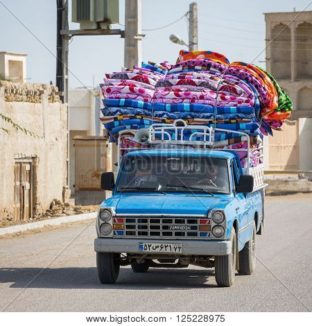 Bandar-e Loft, Qeshm, Iran - December 20, 2015: Pickup car loaded with colorful mattresses rides around the streets calling customers in Bandar-e Loft village, Qeshm, Iran.
