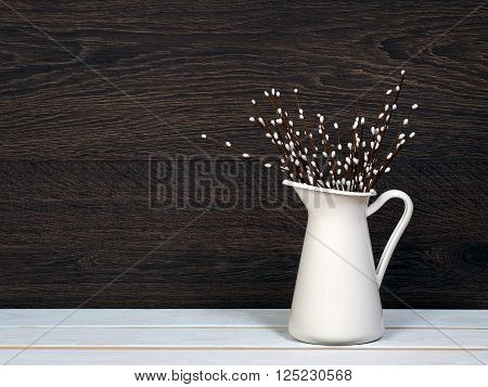 Willow Bunch in white jug. Decorative willow branches. Wood White regiment. Wooden dark wall. interior Detail