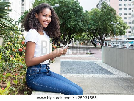 Latin woman with curly hair sending message with phone in the city