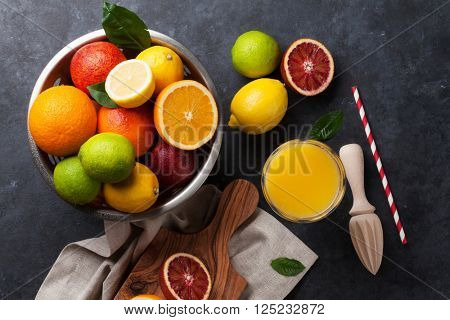 Fresh ripe citruses and juice. Lemons, limes and oranges on dark stone background. Top view