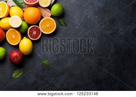 Fresh ripe citruses. Lemons, limes and oranges on dark stone background. Top view with copy space