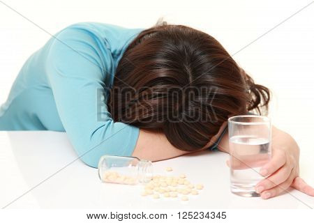 woman suicide with drug pills on white background