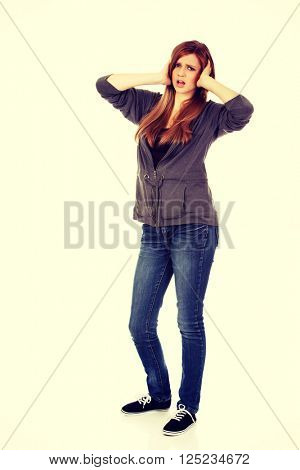 Angry teenage woman covering ears with hands
