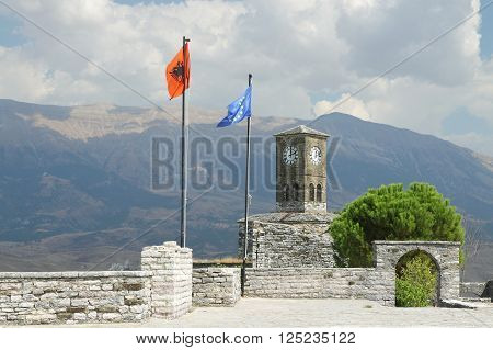 Flags of Albania and of European Union flying on the citadel of Gjirokaster south Albania mountains in the background