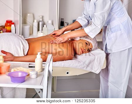 Woman middle-aged take back massage in spa salon with young beautician. Medical cosmetologist.