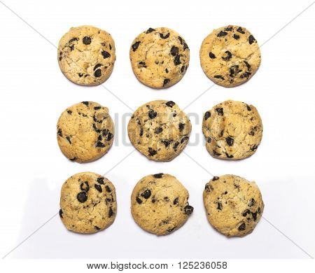Crispy sweet chocolate chip cookies arranged on white background photographed from a high angle in the style Flat Lay