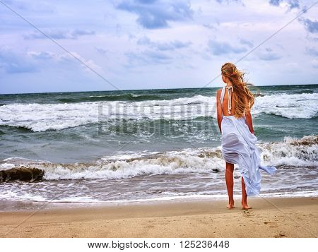 Girl in a white dress on the beach near the sea. Outdoor fashion style.