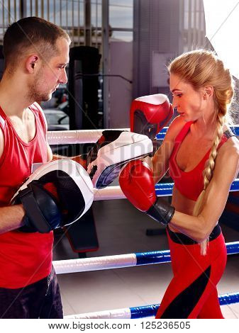 Female boxer  throwing  right cross at mitts with her trainer in ring. Woman and man train in boxing style.