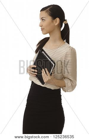 Young businesswoman holding personal organizer, looking right.