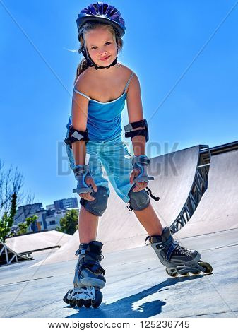 Girl riding on roller skates in skatepark summer outdoor. Child in a blue suit for the rollers.