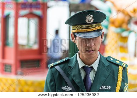 Beijing China - October 14 2013: A Chinese guard from the Beijing Public Security Bureau (PSB) patrolling the area of the Summer Palace Beijing China.